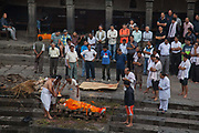 An old man is cremated, his sons lighting the fire and the fire tended to by funeral service men. To burn a body fully takes an estimated 4 hours and hundreds of kilo of wood using butter as fuel. According to Hindu religion and traditions the dead must be burned. Along the Bagmati River next to the Pashupatinath Temple complex are ten alocated spaces for cremation and all day funerals are being held. The bodies are cremated according to custom and the ashes and remains are swept into the holy waters. The Bagmati runs into the Ganges further South and is considered equally holy to Hindus.