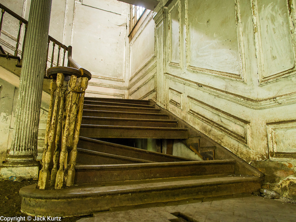07 JUNE 2014 - YANGON, MYANMAR: An interior staircase at the Pegu Club. The Pegu Club in Yangon was the Officers' Club for the British Army when Myanmar was the British colony of Burma. The club, principally made of teak, is now abandoned and in decay. Squaters have moved into the parts of the complex still standing. Yangon has the highest concentration of colonial style buildings still standing in Asia. Efforts are being made to preserve the buildings but many are in poor condition and not salvageable.    PHOTO BY JACK KURTZ