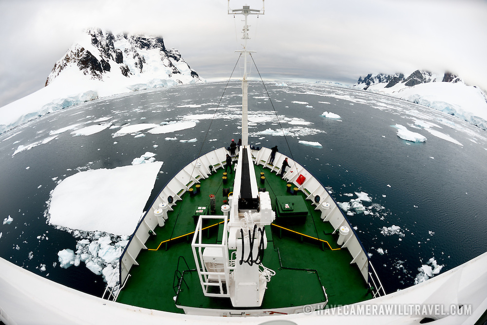 An ice-strengthened ship pushes through scattered plates of sea ice in calm waters in the Lemaire Channel on the western side of the Antarctic Peninsula.