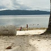 Papua kids playing on the white sandy beach.
