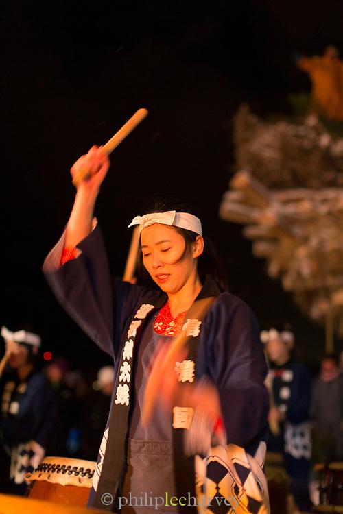 Woman playing drums at traditional festival, Nozawaonsen, Japan