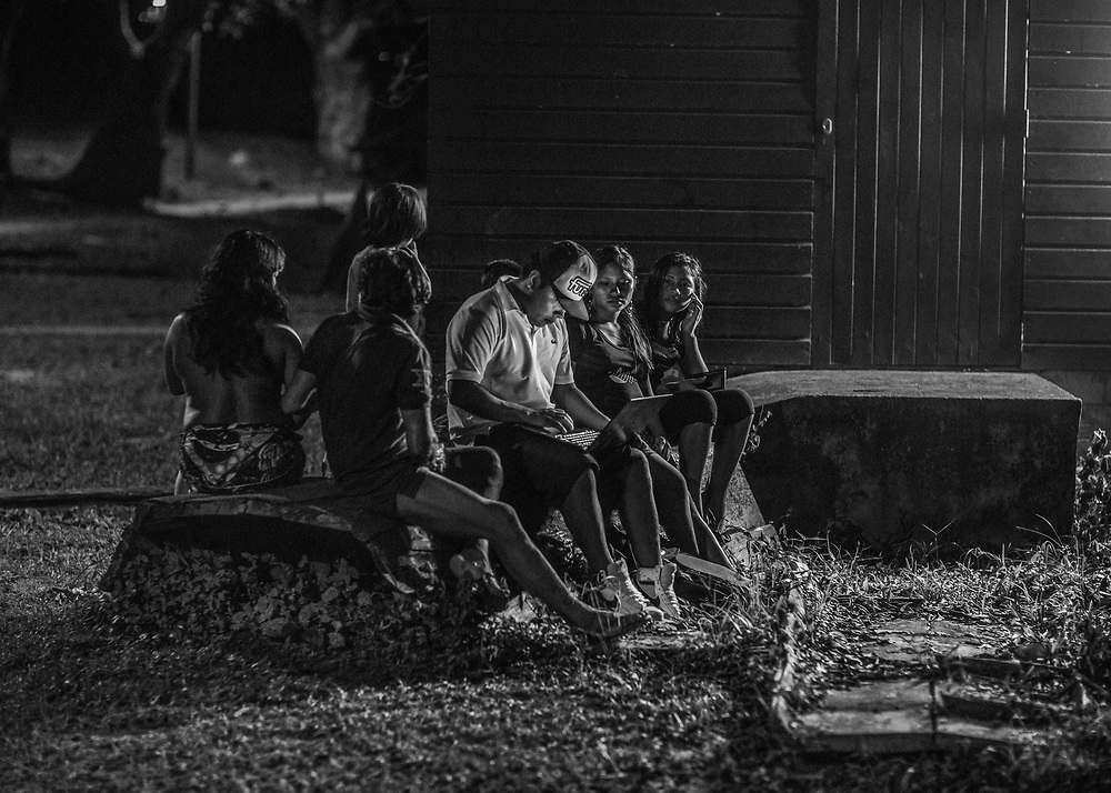 Camopi, Guyane, 2015.<br /> <br /> La récente sédentarisation des populations autochtones de l'Oyapock et la dépendance induite par l'attribution de minima sociaux à titre individuel conduit à la faillite de l'organisation communautaire traditionnelle. La domination économique, sociale, culturelle et politique qu'elles subissent de la part de l'État semble aujourd'hui les laisser sans pouvoir de décision sur leur propre destin. <br /> <br /> Les plus jeunes, acculturés par un système scolaire peu respectueux de leur culture, apprennent dans la langue de la République l'histoire de France et les mathématiques. Du moins les bases, le collège n'a été ouvert à Camopi qu'en 2008, jusqu'alors les enfants étaient scolarisés à Saint-Georges et hébergés dans un home indien, un pensionnat catholique. La fréquentation du lycée oblige de se rendre sur le littoral. Éloignés de leurs familles et de leurs villages, fragilisés par l'isolement et des problèmes identitaires, ce passage se traduit surtout par un taux d'échec scolaire important, des conduites addictives chez les garçons et des grossesses précoces chez les filles. Sans réelle qualification et sans perspective, ils restent généralement à mi-chemin entre deux mondes, abandonnés au mirage des biens de consommation auxquels ils n'ont pas accès.<br /> <br /> À Camopi le taux de suicide des jeunes de moins de 25 ans, il s'agit ici souvent de préadolescents, atteignent des niveaux préoccupants. Une étude de la coordination des Centres de Santé affirme qu'en 2014 la commune est la plus touchée par les tentatives de suicide en Guyane et comptabilise à elle seule 26% des cas recensés dans le département. <br /> <br /> Une famille de Camopi reçoit un neveu brésilien pour les vacances.
