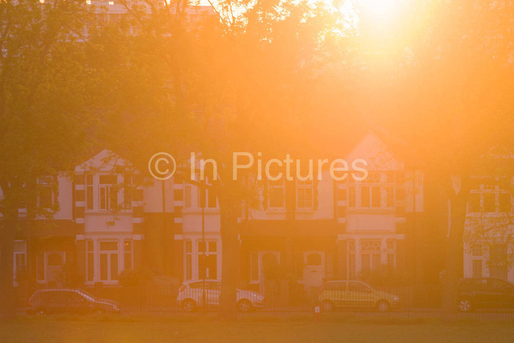 Warm, orange sunlight glare from a setting sun and Edwardian period homes in the south London borough of Lambeth. Strong backlighting by this sunlight gives the scene a cosy, warmth to these houses located on the edge of Ruskin Park/ Houses were built at the turn of the 20th century, an era for extensive period of building just after WW1. The warm light makes for a safe and inviting atmosphere for those considering home ownership with a low-interest mortgage.