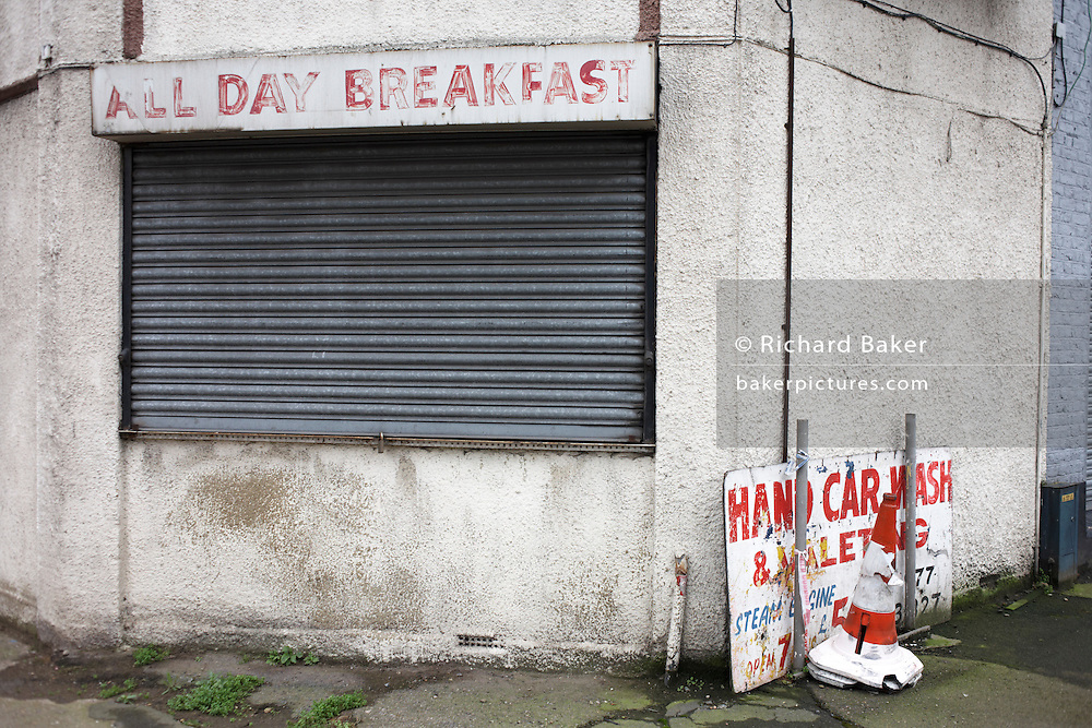 A boarded-up derelict cafe that once served All Day Breakfasts, now on wasteland in Canning Town, Newham..
