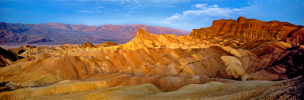 Sunrise accentuates the striking forms of Zabriskie Point, Death Valley National Park, California