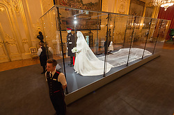 © Licensed to London News Pictures. 25/10/2018. Windsor, UK. Windsor Castle staff The Duchess of Sussex's wedding dress which was created by the British designer Clare Waight Keller Artistic Director at the historic French fashion house Givenchy. The Duke of Sussex uniform is from the Household Cavalry(the Blues and Royals. The outfits are on display at The Royal Collection at Windsor Castle. PLEASE NOTE, THIS PHOTO IS EMBARGOED FOR PUBLICATION UNTIL 00:01 FRIDAY 26 OCTOBER 2018. Photo credit: Ray Tang/LNP