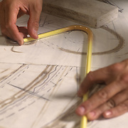Closeup vertical, color shot of a worker's hands positioning neon tube over blueprint layout.