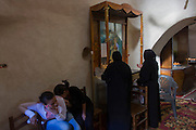 While young Egyptian girls joke among themselves, older Christian women say prayers and make offerings at St Tawdros (St Theodore's) Coptic Orthodox Christian Monastery, Luxor, Nile Valley, Egypt. The Copts are an ethno-religious group in North Africa and the Middle East, mainly in the area of modern Egypt, where they are the largest Christian denomination. Christianity was the religion of the vast majority of Egyptians from 400–800 A.D. and the majority after the Muslim conquest until the mid-10th century. Today, there are an extimated 9-15m Copts in Egypt.
