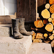 Logs for firewood and a pair of dirty wellies on the doorstep outside a peasant farmer's home in Botiza, Maramures, Romania.