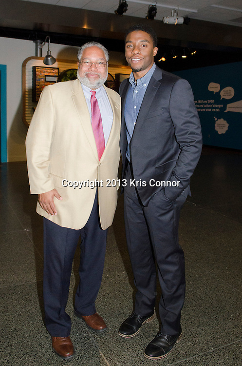 """WASHINGTON, DC - APRIL 15:  Chadwick Boseman, and Lonnie G. Bunch III,  director of the Smithsonian's National Museum of African American History and Culture  pose with Jackie Robinson artifacts during the Washington DC screening of Warner Bro's film """"42"""" at Smithsonian Museum of American History on April 15th, 2013. Guests included star of the film Chadwick Boseman, John Gray, Carol Melton, and Lonnie Bunch. Photo by Kris Connor/Warner Bros"""