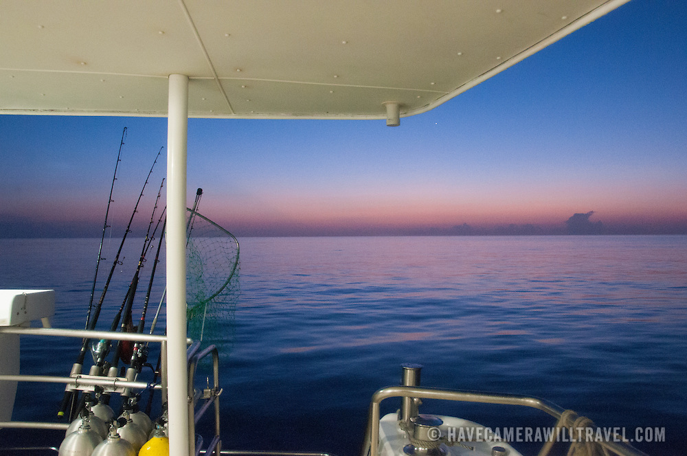 Pink, purple, and blue hues on the horizon just after a colorful sunset on the Great Barrier Reef, Queensland, Australia. In the foreground is part of the deck of a large fishing boat anchored on the reef overnight.