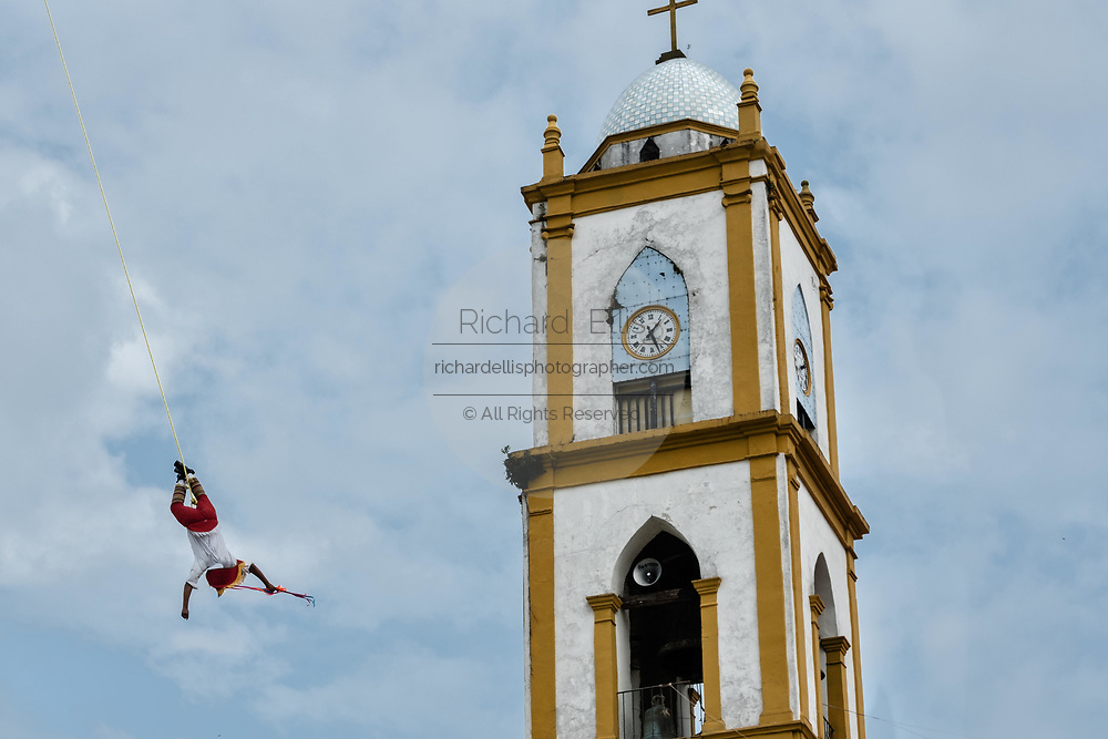 A Volador performs in front of the Church of the Assumption in Papantla, Veracruz, Mexico. The Danza de los Voladores is a indigenous Totonac ceremony involving five participants who climb a thirty-meter pole. Four of these tie ropes around their waists and wind the other end around the top of the pole in order to descend to the ground. The fifth participant stays at the top of the pole, playing a flute and a small drum. The ceremony has been inscribed as a Masterpiece of the Oral and Intangible Heritage of Humanity by UNESCO.