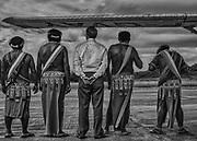 Camopi, Guyane, 2015.<br /> <br /> Monsieur le sous-préfet de l'Est Guyanais et  les  chefs  coutumiers Teko et Wayãmpi de Camopi  attendent  la  visite  de madame la Ministre des Outre-mer.<br /> <br /> A la fin des années 20, la France cherche à créer une alternative à l'essoufflement de la production aurifère en développant l'intérieur guyanais. La loi coloniale de 1930 institue une nouvelle entité administrative, le « Territoire de l'Inini », avec le statut de « nation indépendante sous protectorat ». En 1946, la Guyane devient un département et son dernier gouverneur devenu Préfet décide d'implanter un poste administratif à Camopi sur l'Oyapock dans l'Est guyanais et un autre à Maripasoula, sur le Maroni dans l'Ouest. Dans les années 60, les populations Amérindiennes du haut-Oyapock sont incitées à se regrouper en gros villages pour faciliter les contacts avec l'administration. Les chefs reçoivent le titre de capitaine, ils sont intronisés officiellement lors de voyages à Cayenne. Camopi devient un bourg administratif artificiel, là ou une mission jésuite concentrait déjà les communautés amérindiennes de la région au XVIIIe siècle. <br /> <br /> En 1969, à l'occasion d'un nouveau découpage administratif, le « Territoire de l'Inini » est finalement intégré au département. Entre 1969 à 1987, se succèdent la création de la commune de Camopi, l'élection d'un maire, l'établissement chaotique d'un état civil, la participation aux élections locales, nationales et européennes, la sédentarisation de la population, l'envoi des enfants en pension au home religieux de Saint-Georges pour poursuivre leur scolarité au collège, l'octroi des Allocations Familiales et en 1987, celui du Revenu Minimum d'Insertion. Les Wayãmpi et les Teko sont devenus des citoyens français.<br /> <br /> En 2015, le mot d'ordre officiel est de rendre les populations autochtones maîtres de leur destin, dans le strict cadre de la République. Sur place, la réalité est moins reluisante.