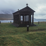 """In 1888 the island was acquired by Sir George's father, John Bullough, a cotton machinery manufacturer and self-made millionaire from Lancashire, England. Rum was used by the family as a hunting estate and when John Bullough died in 1891 he was interred on the west of the island, at Harris Bay, in a rock cut mausoleum. <br /> <br /> Legend has it, that a guest of the Bulloughs remarked that the rock cut mausoleum (having mosaic tiling to the interior) was """"redolent of a public lavatory in Waterloo Station"""".  Sir George, who had been knighted in 1901 and who had set about a programme of improvements on the island which included the building of Kinloch Castle, commissioned a new Grecian inspired family mausoleum (also at Harris Bay).  Upon its completion the original rock cut mausoleum was demolished and the remains of George's late father were reinterred within the new monument.<br /> The body of John Bullough was joined by his son, Sir George Bullough who died in France in 1939 and that of his wife, Lady Monica who died in 1967 at the age of 98.  Though Sir George and Lady Monica's daughter, Hermione, is not interred therein her name was inscribed on the side of her mother's tomb during recent conservation works (completed 2006).<br /> Though the island and castle are now owned by Scottish Natural Heritage the mausoleum remains in hands of the Bullough Trustees."""