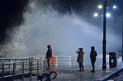 © London News Pictures. 08/02/2016. Aberystwyth, UK.<br /> Members of the public watch as the evening  high tide reaches its peak and waves continue to hit the sea defences at Aberystwyth on the west Wales coast. Photo credit: Keith Morris/LNP