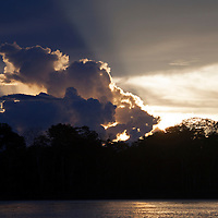 South America, Peru, Amazon. Setting sun lights the sky and clouds over the Amazon.