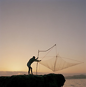 Fisherman using an old chinese style fishing net, Puglia, Italy