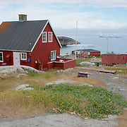 A colorful building with a backdrop of icebergs outside of Qeqertarsuaq, Greenland.