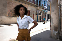 A girl in a school uniform walking in the shade on a street in old Havana .