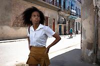 A girl in a school uniform walking in the shade on a street in old Havana .