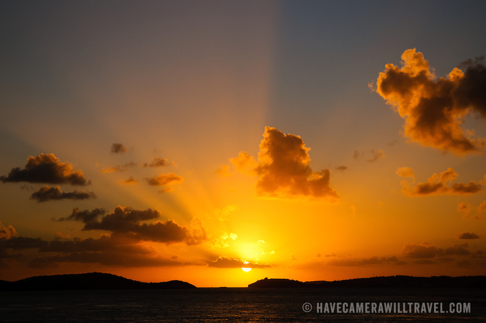 A beautiful Caribbean sunset from St. John in the US Virgin Islands as the sun disappears below the horizon behind St. Thomas.