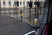 During a seasonal rain shower, a lady wearing a yellow coat pauses to cross the road at St. Georges Circus in Southwark, on 9th May 2019, in London, England.