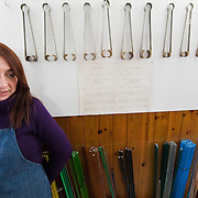 VENICE, ITALY - DECEMBER 18:  Elena Rosso a glass  artist in Murano poses in front of  coloured glass rods and a selection of mashers on December 18, 2010 in Venice, Italy. There are only few glass artists is Italy and the face continuous challanges in a traditionally male dominated field.
