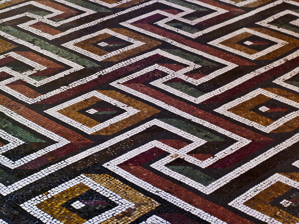 Floor pattern in the room of the Capitoline wolf sculpture is a meandering Greek key interspersed with dots and squares.