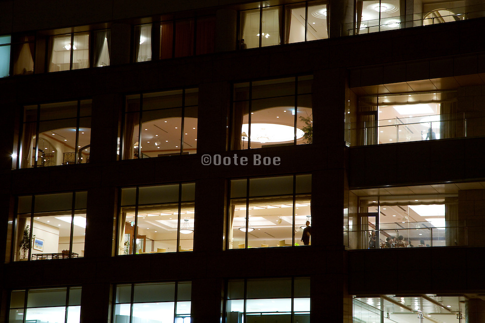 hotel and office building at night with one person standing in the window, Tokyo Japan