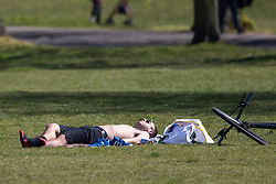 © Licensed to London News Pictures. 23/04/2021. London, UK. A man sunbathes during sunny weather in Greenwich Park in south east London. Temperatures are expected to rise with highs of 16 degrees forecasted for parts of London and South East England today . Photo credit: George Cracknell Wright/LNP