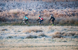 © Licensed to London News Pictures. 04/11/2020. London, UK. Cyclists ride through a frost covered landscape at sunrise in Richmond Park, south west London on a cold Autumn morning. Photo credit: Ben Cawthra/LNP