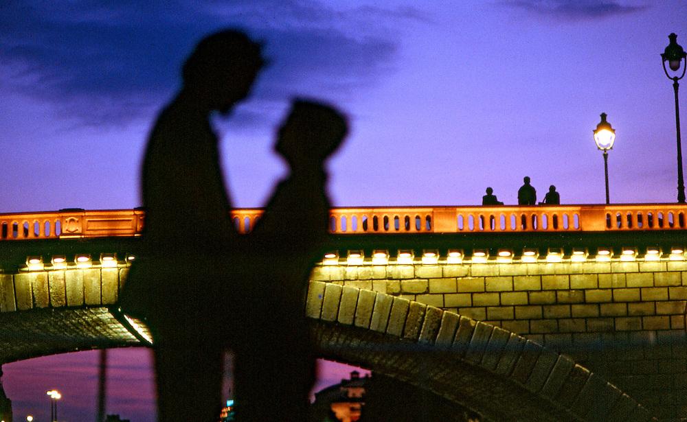Un couple d'amoureux sur un bateau, passant sous le Pont Neuf, à la nuit tombée, Paris, Paris-Ile-de-France, France.<br /> A lovers' couple on a boat passing under the Pont-Neuf, at night, town of Paris, Paris-Ile-de-France region, France.