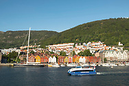 A tour boat in the harbour passing the colourful buildings of Bryggen, Bergen, Norway, Europe