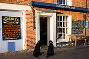 Obedient Labrador dogs wait outside Gurneys Fish Shop in Burnham Market in North Norfolk, UK