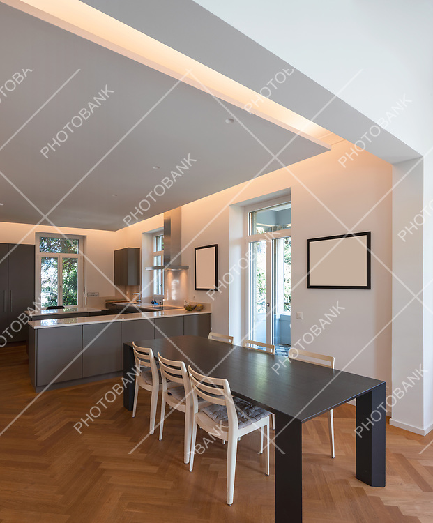Modern kitchen with window and parquet. Large table with chairs. Nobody inside