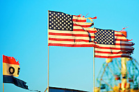 Two torn American flags and the remaining part of an Open flag blowing in the wind. Coney Island.