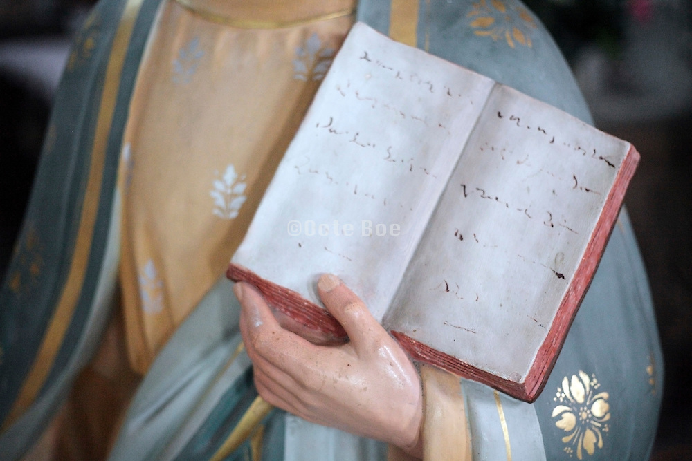 statue figure hand holding a open book with handwritten text