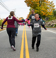 "Elaine Barros and Patty Colby give Steve and Caden Tucker a high five for ""Team Di Gleason"" as they pass each other on the Tanger Outlet Fit for a Cure walk held Sunday morning.  (Karen Bobotas/for the Laconia Daily Sun)"