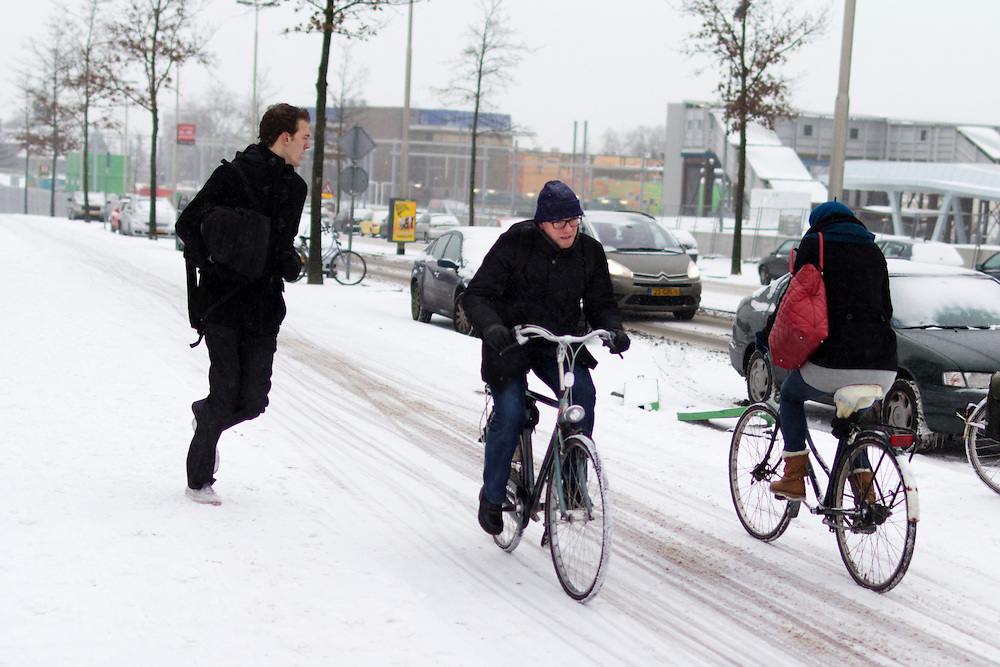 Twee fietsers rijden op de Amsterdamseweg in Arnhem door de sneeuw, terwijl een jongen zich haast om op tijd op het station te zijn.<br /> <br /> Tow cyclists are riding at the Amsterdamseweg in Arnhem in the snow, while a boy is running to be on time at the railway station.
