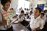 Out-reach peer-peer education to school children. Here Ny Sreay Leak, 16 goes through the LAC produced flip chart of petty crimes and social issues and talk them over with the children.Legal Aid Cambodia  tries through out-reach education in schools to prevent children from falling into crime and teach them their rights.LAC also offer legal aid to children arrested and sent to prison, many of them without any legal representation.