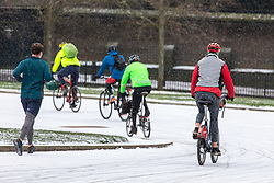 © Licensed to London News Pictures. 09/02/2021. London, UK. Cyclists commute to work in a snowy Hyde Park Corner, London this morning as Storm Darcy hits the South East with yet more snow and freezing temperatures today. The Met Office have issue numerous weather warnings for heavy snow and ice with disruption to travel, power cuts and possible stranded vehicles as the bad weather continues throughout the country.  Photo credit: Alex Lentati/LNP