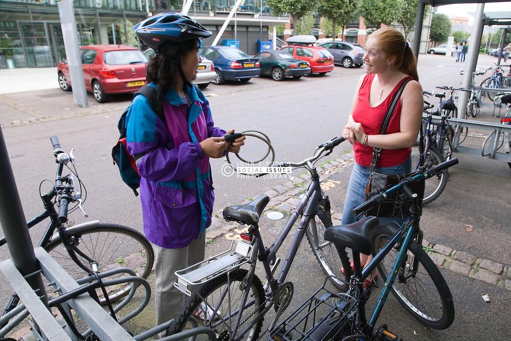 Woman locking up her bike chatting in a works bike shed,