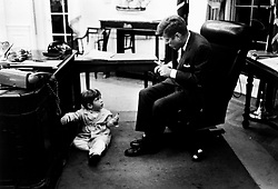 John F. Kennedy, the nation's 35th President, would have turned 100 years old on May 29, 2017. With the centennial anniversary of John F. Kennedy's birth, the former president's legacy is being celebrated across the nation. PICTURED: 1963 - Washington, District of Columbia, U.S. - JOHN F KENNEDY JR peeks out from the door in the Resolute Desk in the Oval Office at the White House as his father, President JOHN F KENNEDY reads papers on his desk. Exact date unknown. (Credit Image: © John F. Kennedy Library/ZUMAPRESS.com)