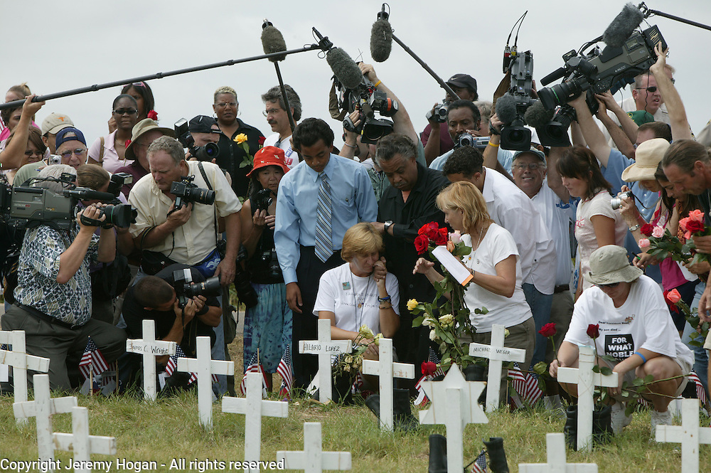 The Reverend Al Sharpton Jr. comforts Cindy Sheehan near a cross representing Casey Sheehan at Camp Casey II during after a Sunday morning service during her vigil.