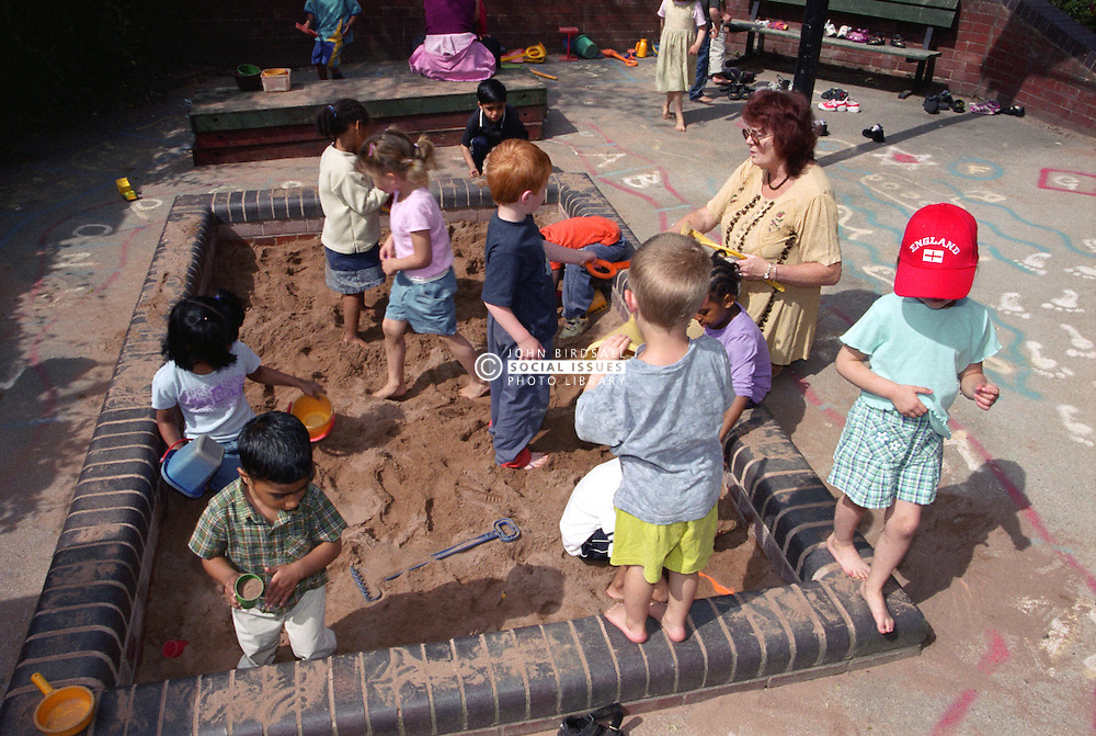 Multiracial group of nursery school children using buckets and spades to play with sand in playground sandpit,