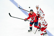 Washington Capitals forward T.J. Oshie and Carolina Hurricanes forwards Andrei Svechnikov and Teuvo Teravainen look up at the puck at Capital One Arena on January 13, 2020.