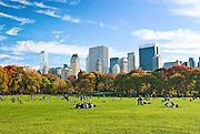 People relax in Sheep Meadow, Central Park, New York City in Autumn, looking towards the Central Park South skyline.