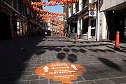 Social distancing signs on the pavement on Lisle Street as Chinatown remains very quiet with a few people visiting Chinese restaurants to pick up food and to see the red lanterns on 25th June 2020 in London, England, United Kingdom. As the July deadline approaces and government will relax its lockdown rules further, the West End remains quiet, while some non-essential shops are allowed to open with individual shops setting up social distancing systems.