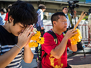 19 AUGUST 2015 - BANGKOK, THAILAND:       People who lost family members in the terror bombing of Erawan Shrine pray during the reopening of the shrine. Erawan Shrine in Bangkok reopened Wednesday morning after more than 20 people were killed and more than 100 injured in a bombing at the shrine Monday, August 17, 2015. The shrine is a popular tourist attraction in the center of Bangkok's high end shopping district and is an important religious site for Thais. No one has claimed responsibility for the bombing.     PHOTO BY JACK KURTZ