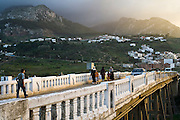 Pedestrians and cars commute across a bridge over the Martil River in the outskirts of Tetouan, Morocco, on October 27, 2007. The Rif Mountains are visible in the background.